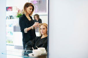 Hairdresser curling customer's hair in salonの写真素材 [FYI02167412]