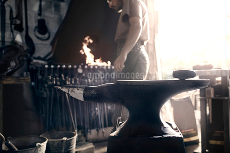 Blacksmith at fire behind anvil in forgeの写真素材 [FYI02167427]
