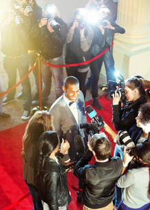 Celebrity being interviewed and photographed by paparazzi photographer at red carpet eventの写真素材 [FYI02167450]