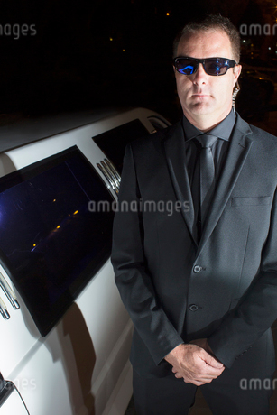 Portrait of serious bodyguard in sunglasses outside limousine at eventの写真素材 [FYI02167462]