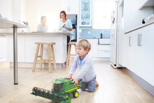 Women cooking in kitchen while boy plays with toy tractor on floorの写真素材 [FYI02167466]