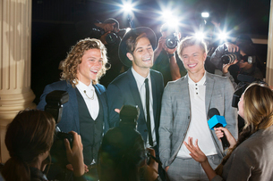 Smiling celebrities being interviewed and photographed by paparazzi photographers at eventの写真素材 [FYI02167474]