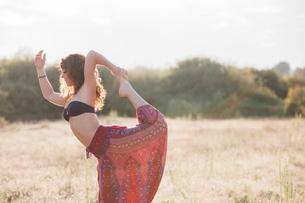 Boho woman in king dancer yoga pose in sunny rural fieldの写真素材 [FYI02167524]