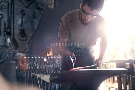 Blacksmith forging hot iron at anvil in forgeの写真素材 [FYI02167528]