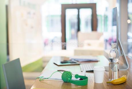 Headphones, water bottle, coffee and banana on desk with computerの写真素材 [FYI02167570]