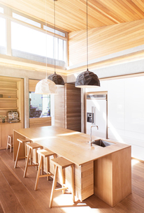 Modern pendant lights hanging over wooden kitchen islandの写真素材 [FYI02167592]