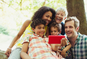 Multi-generation family taking selfie with camera phone in woodsの写真素材 [FYI02167645]