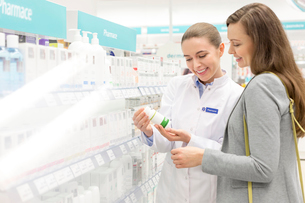 Pharmacist and customer reviewing label on bottle in pharmacyの写真素材 [FYI02167650]
