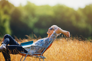 Carefree senior woman relaxing with book in sunny fieldの写真素材 [FYI02167685]