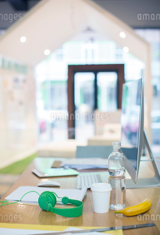 Headphones, water bottle, coffee and banana on desk with computerの写真素材 [FYI02167686]