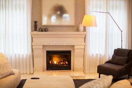 Illuminated floor lamp near marble fireplaceの写真素材 [FYI02167687]