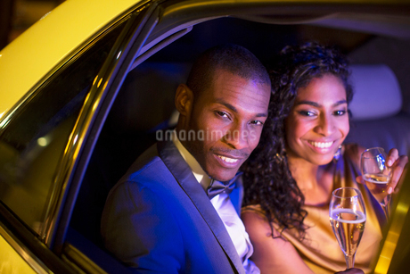 Well-dressed couple drinking champagne inside limousineの写真素材 [FYI02167695]