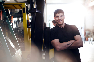 Portrait confident mechanic leaning on forklift in auto repair shopの写真素材 [FYI02167706]