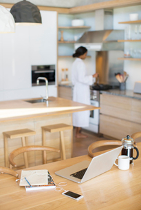 Laptop, French press coffee, cell phone and notebook on kitchen tableの写真素材 [FYI02167725]
