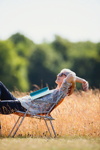 Carefree senior woman relaxing with book in sunny fieldの写真素材 [FYI02167748]