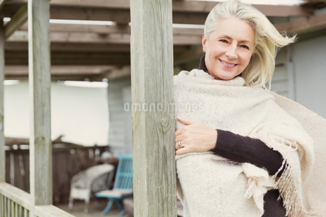 Portrait smiling senior woman wearing shawl on windy porchの写真素材 [FYI02167777]