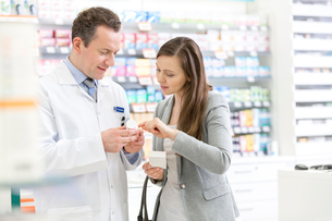 Pharmacist and customer reviewing prescription label in pharmacyの写真素材 [FYI02167779]