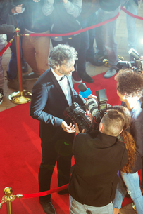 Celebrity being interviewed and photographed by paparazzi photographers at red carpet eventの写真素材 [FYI02167817]