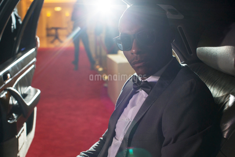 Portrait of serious celebrity in sunglasses inside limousine arriving at red carpet eventの写真素材 [FYI02167819]