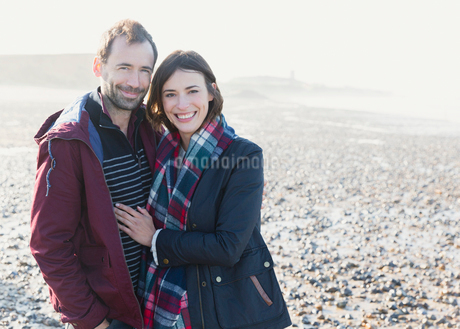 Portrait smiling couple hugging on sunny rocky beachの写真素材 [FYI02167837]