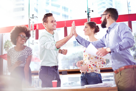 Business people high fiving in meetingの写真素材 [FYI02167850]