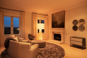 Illuminated floor lamp in living room with fireplaceの写真素材 [FYI02167853]