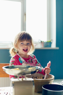 Smiling girl baking with mixing bowl in kitchenの写真素材 [FYI02167913]