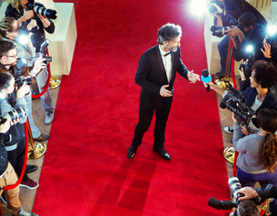 Celebrity on red carpet being interviewed and photographed by paparazziの写真素材 [FYI02167914]