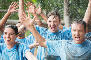 Enthusiastic team cheering in rain at boot campの写真素材 [FYI02167944]