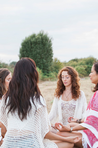 Boho women meditating in circle in rural fieldの写真素材 [FYI02167950]