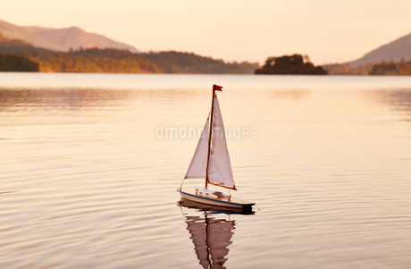 Toy sailboat in tranquil lake at sunrise, Lake District, Cumbria, Englandの写真素材 [FYI02167959]