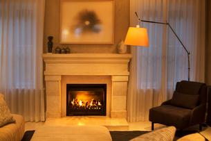 Illuminated floor lamp next to marble fireplaceの写真素材 [FYI02167977]