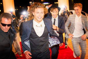 Enthusiastic celebrities arriving and running from paparazzi at red carpet eventの写真素材 [FYI02167979]