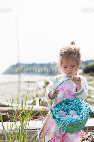 Girl gathering Easter eggs in basket on beachの写真素材 [FYI02167986]