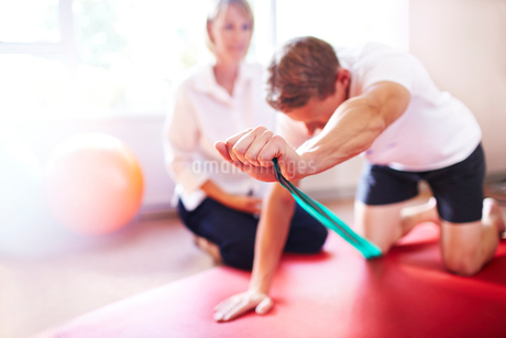 Physical therapist guiding man pulling resistance bandの写真素材 [FYI02167989]