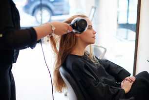 Hairdresser drying customer's long hair in salonの写真素材 [FYI02168008]