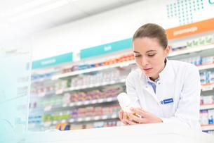 Pharmacist reading label on bottle in pharmacyの写真素材 [FYI02168032]