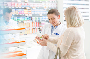 Pharmacist and customer reviewing label on box in pharmacyの写真素材 [FYI02168040]