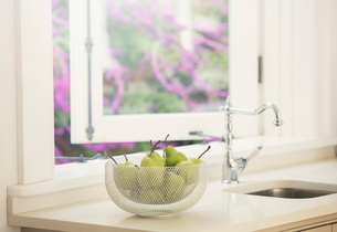 Pears in bowl on kitchen counterの写真素材 [FYI02168073]