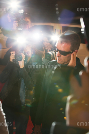 Bodyguard surrounded by paparazzi photographers at eventの写真素材 [FYI02168091]