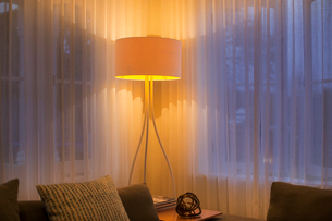 Illuminated floor lamp at window with sheer curtainsの写真素材 [FYI02168111]