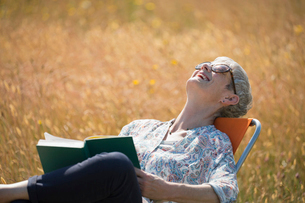 Senior woman reading book and laughing with head back in sunny fieldの写真素材 [FYI02168137]