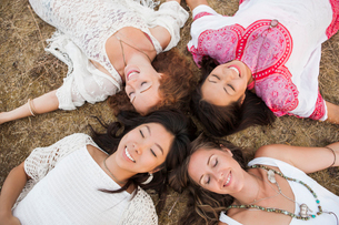 Overhead view of smiling boho women laying in circle with eyes closedの写真素材 [FYI02168143]