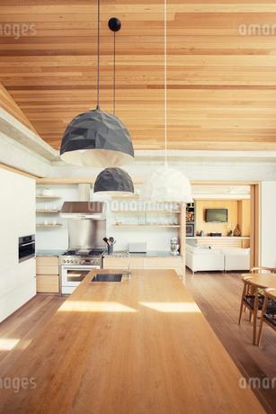 Modern pendant lights over long wood kitchen islandの写真素材 [FYI02168147]