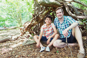 Portrait smiling father and son in woodsの写真素材 [FYI02168173]