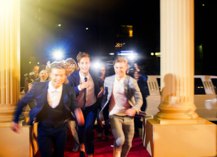 Enthusiastic celebrities arriving and running from paparazzi photographers at red carpet eventの写真素材 [FYI02168176]