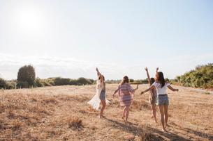 Carefree boho women dancing in sunny rural fieldの写真素材 [FYI02168208]