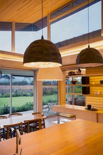 Illuminated modern pendants hanging over wood kitchen islandの写真素材 [FYI02168241]