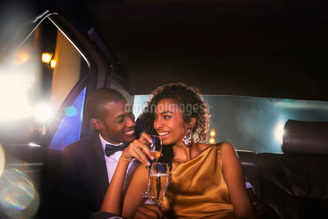 Celebrity couple drinking champagne inside limousine outside eventの写真素材 [FYI02168282]