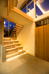 Illuminated modern stairs off foyer in luxury houseの写真素材 [FYI02168291]